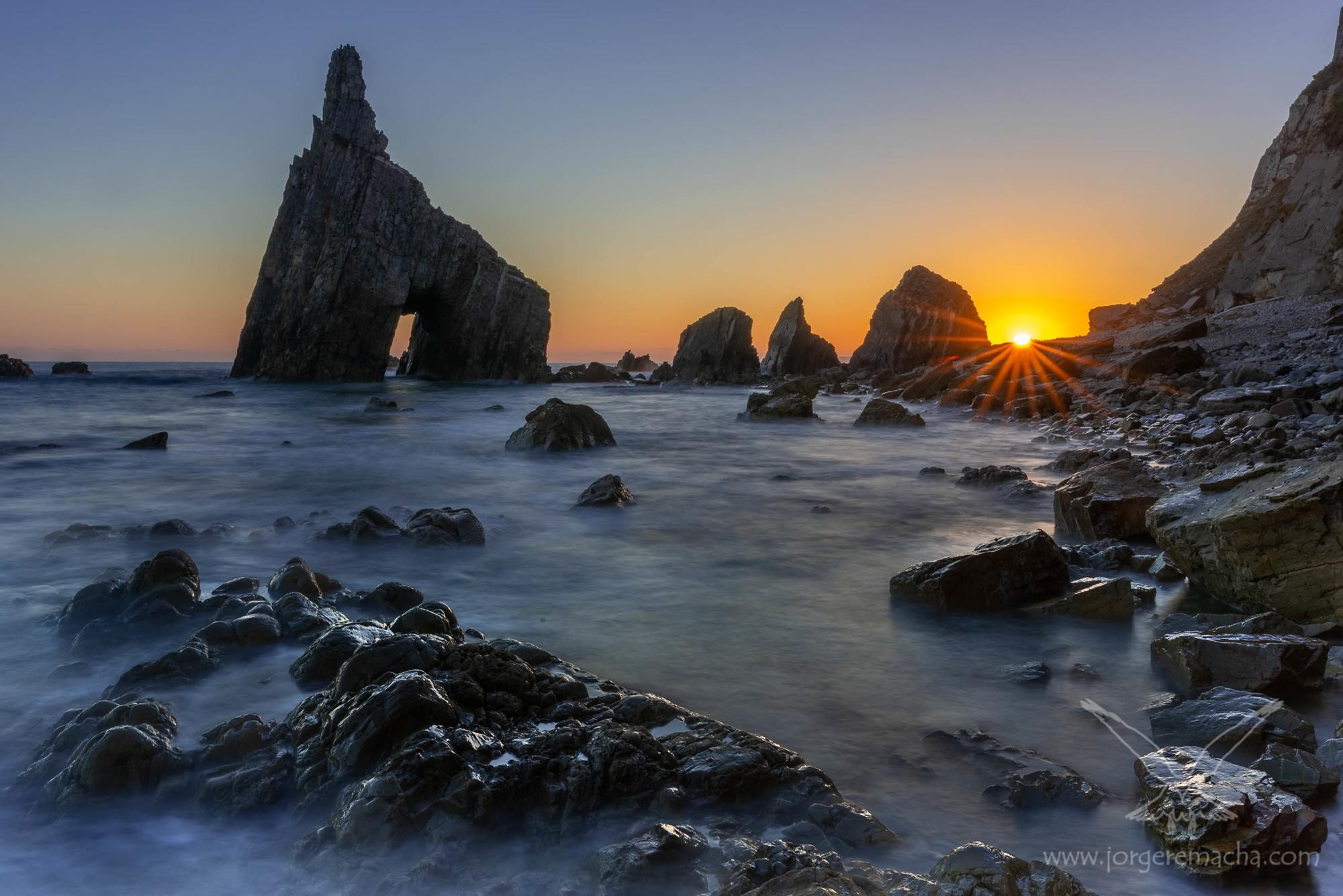 Costa de Cadavedo al amanecer con peña horadada
